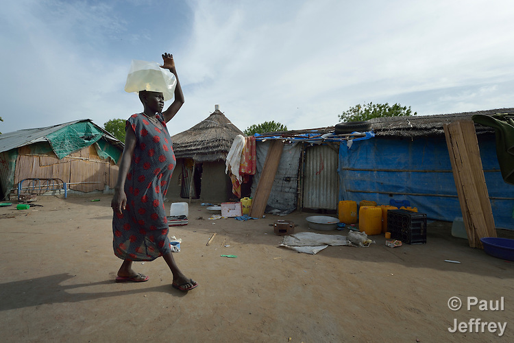 Mou Leu Chol carries water to her home in Bor, a city in South Sudan's Jonglei State that has been the scene of fierce fighting in recent months between the country's military and anti-government rebels. After fighting broke out in mid December 2013, control of the town changed hands four times in a few weeks. ACT Alliance members were among the first humanitarian agencies to enter the city in January 2014, and are providing services to thousands of people who are cautiously returning home to the troubled city. Chol came to Bor in March 2014 to escape continued fighting in nearby Duk County. She and her husband assembled their new home out of the scraps of building materials they found here. The water container she is using is one of several items she received in a household package she received from Dan Church Aid and the Lutheran World Federation, both members of the ACT Alliance.