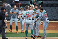 Chad Crosbie (35) of the Miami Hurricanes is greeted at home plate by his teammates after hitting a home run against the Wake Forest Demon Deacons at David F. Couch Ballpark on May 11, 2019 in  Winston-Salem, North Carolina. The Hurricanes defeated the Demon Deacons 8-4. (Brian Westerholt/Four Seam Images)