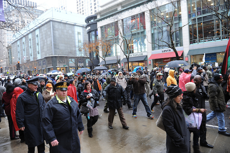 """Protesters take to Michigan Avenue, Chicago's """"Magnificent Mile"""" and longest shopping street, to protest three days after the release of a dash cam video documenting the killing of Laquan McDonald by Chicago Police Officer Jason Van Dyke, who has been charged with his murder, on Black Friday, the busiest shopping day of the year, in Chicago, Illinois on November 27, 2015.  Van Dyke fired 16 shots at McDonald and fired 13 of those shots after McDonald was on the ground and only stopped after his colleague told him to stand down; a journalist for outlet DNA Info sued the City of Chicago for release of the dash cam video, which the city released only after ordered to do so by a judge last week."""
