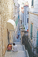 Two people sitting on the stairs of a steep narrow street in front of a hotel Dubrovnik, old city. Dalmatian Coast, Croatia, Europe.