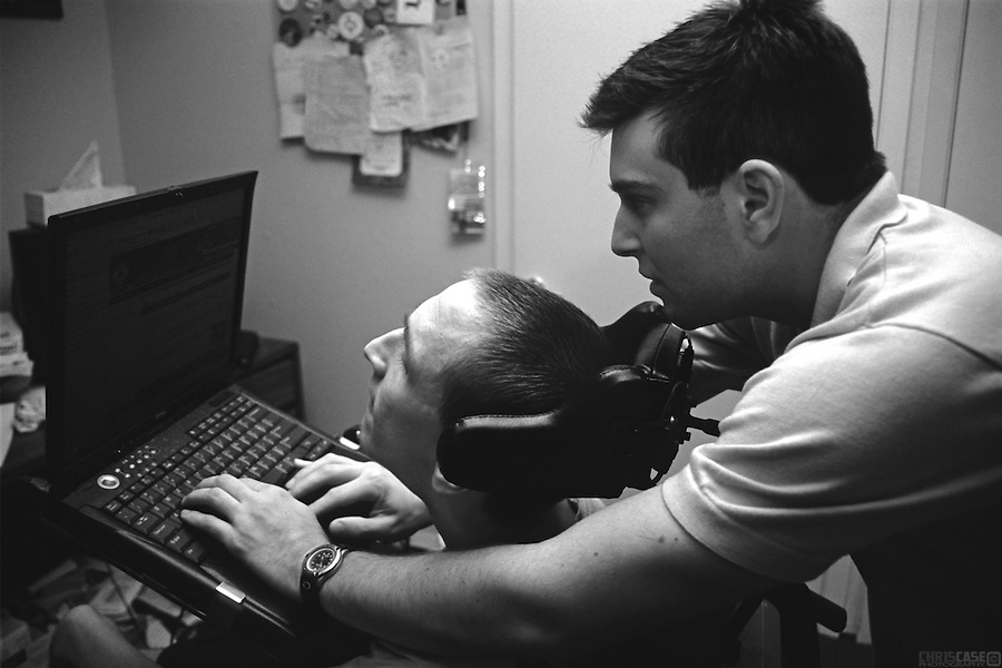 Sean Pevsner's assistant, Michael Galante, helps him set up his computer, which he can control with the paddles in his head brace.<br /> <br /> Sean Pevsner was born with severe cerebral palsy. Sean is in his final year of law school at the University of Texas.