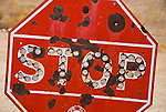 Old, shot-up and rusting Auto Club stop sign with cat eye reflectors in rural Nevada