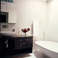 The contemporary guest bathroom is fitted with a spoon wash basin and bath by Agape