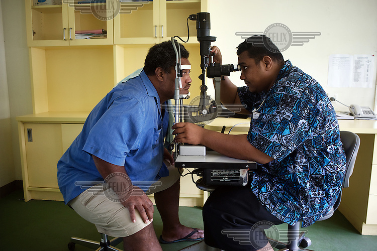 Dr Chris, a Tuvaluan who was trained in Fiji, uses a slit lamp to examinine a patient's eye in the Princess Margaret Hospital that was built with Japanese aid and opened in 2004.