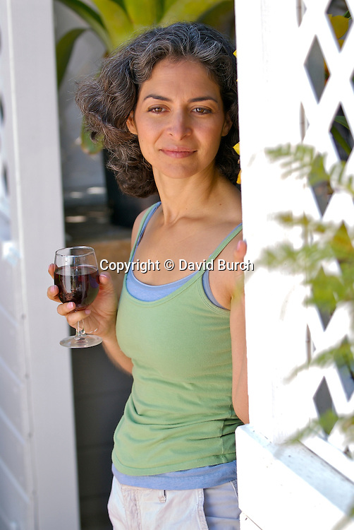 Mature woman holding wineglass, thoughtful