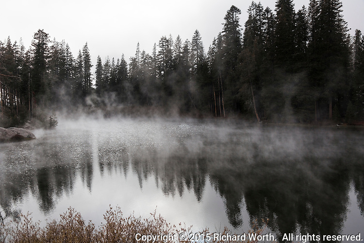 Steam rises from a small lake alongside the westbound rest area at the summit of Donner Pass, California.