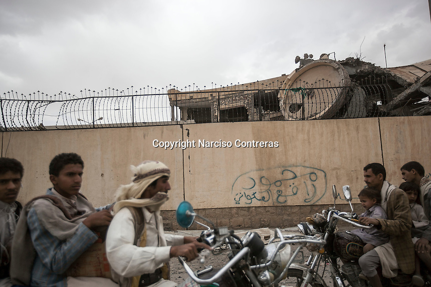 Wednesday 15 July, 2015: Civilians drive by pass to a building damaged by a bomb blast in one downtown of Sa'dah, a city subdued to heavy bombarments carried out by the Saudi-led coalition in the northern province of Sa'dah, the stronghold of the Houthi's movement in Yemen. (Photo/Narciso Contreras)