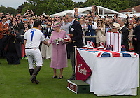 Cartier Queen Cup winner Aiyawatt Srivaddhanaprabha (King Power Foxes) of Thailand collects the Cup from Her Majesty the Queen and Arnaud M. Bamberger, Executive Chairman during the Cartier Queens Cup Final match between King Power Foxes and Dubai Polo Team at the Guards Polo Club, Smith's Lawn, Windsor, England on 14 June 2015. Photo by Andy Rowland.