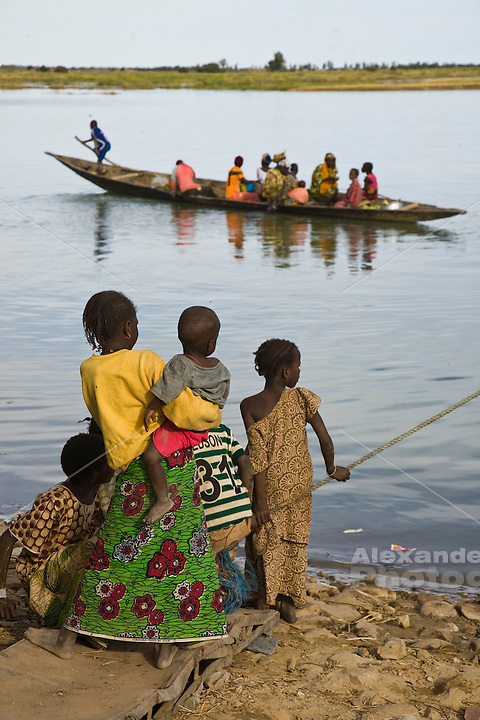 Korioume, Mali, 2009 - A Family waits for a lift across the Niger  River. A small rowboat operated as a ferry carries passengers to a neighboring village near Timbuktu, Mali