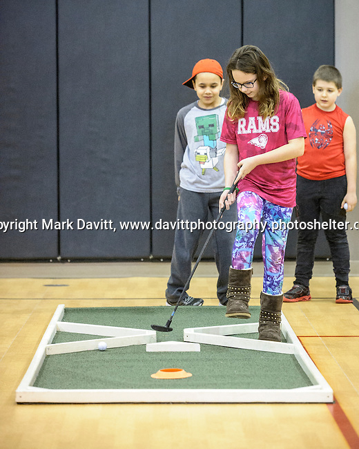 Kayla Vest watches her ball move toward the hole while Gabriel Bridges and Joshua Schonkaes take note of her skills at the fourth annual 4th Altoona Elementary Golf in the Halls was held Jan. 28. Participants enjoyed a breakfast and  two, 18-hole mini-golf courses throughout the school's classrooms, hallways and gymnasiums.