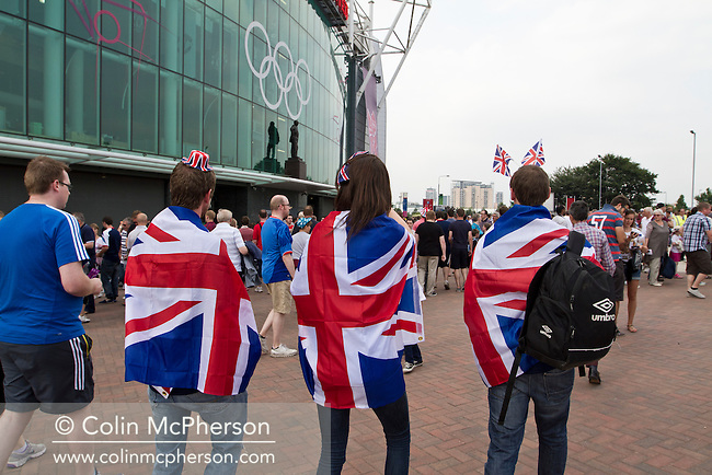 Three supporters of the Great Britain football team walking towards Manchester United's Old Trafford stadium prior to the Men's Olympic Football tournament matches at the venue. The double header of matches resulted in Uruguay defeating the United Arab Emirates by 2-1 while Great Britain and Senegal drew 1-1. Over 72,000 spectators attended the two Group A matches.