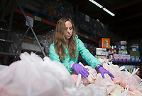 """Emily Hackett of Springdale organizes food to be distributed, Thursday, March 19, 2020 at the Samaritan Community Center in Rogers. Check out nwaonline.com/200320Daily/ for today's photo gallery.<br /> (NWA Democrat-Gazette/Charlie Kaijo)<br /> <br /> In response to the covid-19 crisis, Samaritan decided to convert all of their feeding operations to drive through operations. They started on Monday in Springdale and expanded to Rogers on Tuesday. They are running their Cafe by providing hot meals, running their market by providing groceries and running their snack pack program by providing snack packs along with the groceries people pick up. Compared to a normal week, they've doubled their numbers in Rogers and tripled their numbers in Springdale. Running Monday through Thursday. """"We're trying to do the same thing we always do. We're just serving more people,"""" said Debbie Rambo, executive director. Since revenue is down from their thrift stores, their main funding sources, they are asking people to donate by visiting samcc.org. People can also donate over the phone or they can mail a check to P.O. Box 939 in Rogers, 72757"""