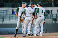 Fort Wayne TinCaps pitching coach Burt Hooton (26) talks to pitcher Max Fried as catcher Rodney Daal and first baseman Diego Goris (7) listen in during a game against the Great Lakes Loons on August 19, 2013 at Dow Diamond in Midland, Michigan.  Great Lakes defeated Fort Wayne 12-5.  (Mike Janes/Four Seam Images)
