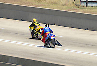 Sept. 22, 2012; Ennis, TX, USA: NHRA pro stock motorcycle rider Scott Pollacheck (near lane) has a wild ride when his tire came off the rim and has a close call with Karen Stoffer during qualifying for the Fall Nationals at the Texas Motorplex. Mandatory Credit: Mark J. Rebilas-