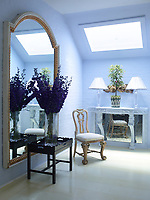 In one corner of the dining room, an arrangement of purple delphiniums in a tall glass vase stands on a tray table; a large mirror hangs on the wall behind. A skylight allows light to fall on a console table.