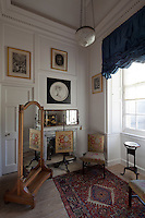 A bedroom of dressing room furnished with an antique free-standing mirror and matching needlepoint chair and firescreen