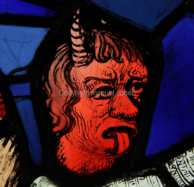 Detail of the devil stealing Job's flocks in order to test his devotion to God, stained glass window, 13th century, originally from the Sainte Chapelle, now in the Musee de Cluny or the Musee National du Moyen Age, Paris, France. The devil has a red face with horns and his tongue sticking out. The Sainte Chapelle is a 13th century royal medieval Gothic chapel on the Ile de la Cite. Picture by Manuel Cohen
