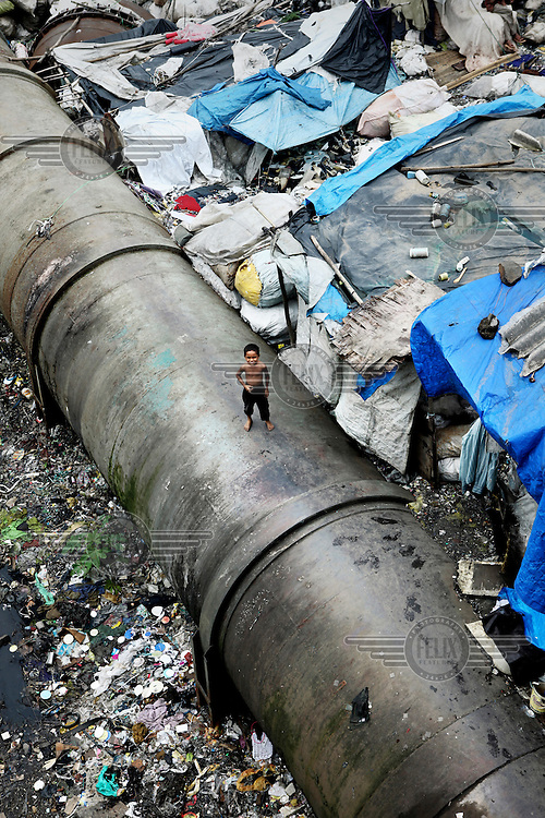 A water pipe running through  Dharavi. This slum consists of 175 hectares of small alleys sustaining  more than a million residents. The water pipe is transporting water towards more affluent areas of Mumbai. In Dharavi people have very limited access to piped water and where it is available the flow often runs for a few hours each day. Slum dwellers frequently suffer from diseases attributed to poor water and sanitation facilities.