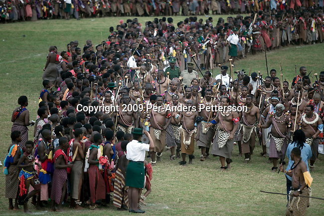 LUDZIDZINI, SWAZILAND - AUGUST 31: King Mswati III dances in front of young virgins at a traditional Reed dance ceremony at the stadium at the Royal Palace on August 31, 2009, in Ludzidzini, Swaziland. About 80.000 virgins from all over the country attended this yearly event, the biggest in Swazi culture. It was founded to celebrate the beauty of Swazi women and girls. King Mswati III, and absolute monarch, was born in 1968 and he has 14 wives and many children. The king danced with his men in front of the 80.000 girls. Many of the girls hope to get noticed by the king and to be chosen as a future wife, a ticket from poverty and into a life of privilege and luxury. The country is one of the poorest in the world and it is struggling with a high prevalence of HIV-Aids and severe poverty. (Photo by: Per-Anders Pettersson)...