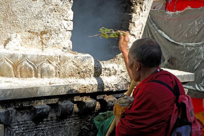 Tibetan Buddhist pilgrim throwing juniper twigs into an incense burner on the Barkhor pilgrim circuit around the Jokhang Temple, Lhasa, Tibet.