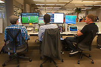 San Francisco, CA - Tuesday, July 1, 2014: (Left to right) Andrew Hubbs, Dane Hurtubise and Greg Smith watch the USA vs. Belgium World Cup Round of 16 game on their computers during lunch at Pivotal Lab offices South of Market in San Francisco.