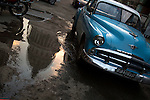 HAVANA, CUBA -- MARCH 25, 2015:   The National Capitol Building is reflected in a puddle as a classic Plymouth car drives by in Havana, Cuba on March 25, 2015. Photograph by Michael Nagle