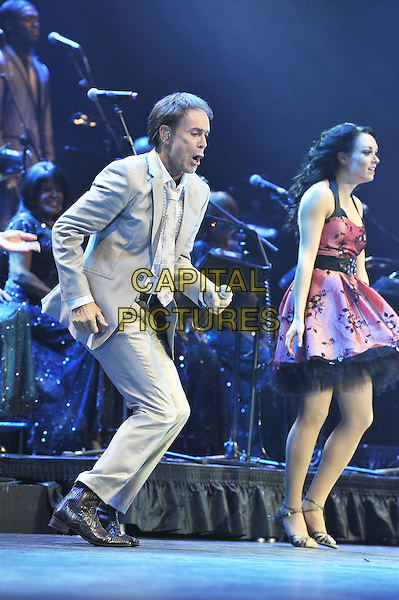 Cliff Richard.Performing live in concert at the O2 Arena, Greenwich, London, England. 25th October 2011.stage gig performance music on full length beige grey gray suit jacket tie dancing side profile backup dancers funny.CAP/MAR.© Martin Harris/Capital Pictures.