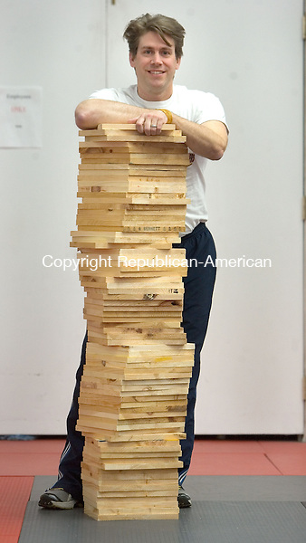 SOUTHBURY, CT. 12 February 2013-021213SV12-Leif Becker, a karate instructor, stands with a pile of pine boards at the Southbury Academy of Karate in Southbury Tuesday. Becker will attempt to set a world record in September by breaking 100,000 pine boards in 24 hours. He hopes to raise $7 million for children's charities..Steven Valenti Republican-American