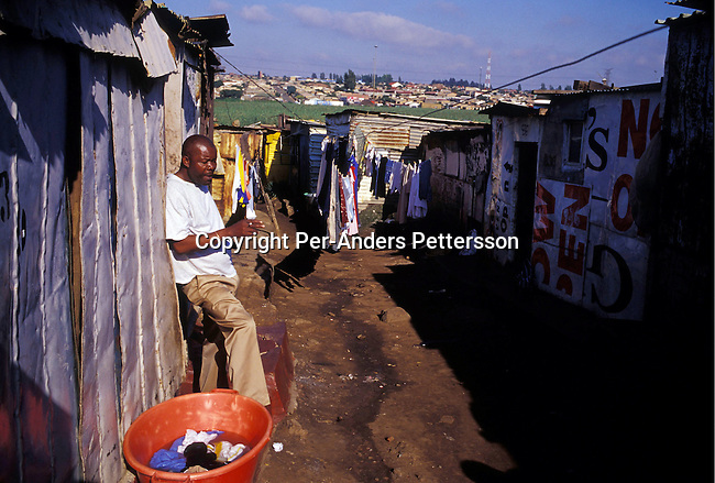 SOWETO, SOUTH AFRICA - FEBRUARY 28: An unidentified man smokes a cigarette early in the morning outside his house on February 28, 2004 in Chris Hani, a poor squatter camp in Soweto outside Johannesburg, South Africa. The government promised to build one million houses during the election in 1994 and about 1,7 million houses have been built. Still the housing backlog are estimated to about 6-7 million units, making it still a dream for many poor people in South Africa to own a house. Many poor South African's still live in shacks without electricity and running water..(Photo: Per-Anders Pettersson/ iAfrika Photos.....