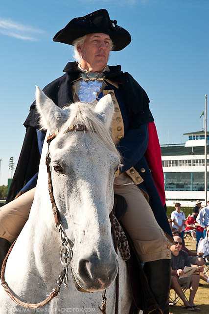 George Washington, as portrayed by Mark Collins, sits on his horse and looks out over the North Houston Tea Party Rally at Sam Houston Race Park