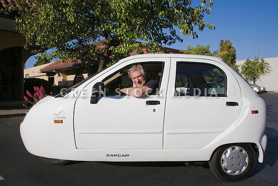 A driver in a white Zap Xebra Zapcar Electric Sedan which seats up to four people and can travel at up to 40 mph (65 kmph) and up to 25 miles per charge (40km). It is classified as a 3 wheel motorcycle (zero emission vehicle). Mountain View, California, USA