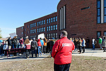 North Bellmore; New York; USA. March 14; 2018. Security Guard in red jacket watches as Mepham High School students, protesting gun violence and some holding protest signs, walk out of class for 17 minutes; from 10:00 am to 10:17 am EST; one minute for each student shot and killed last month in a Parkland, Florida, high school. This was part of a nationwide walkout in soildarity with student shooting victims, and a demand for U.S. laws to reduce gun violence.