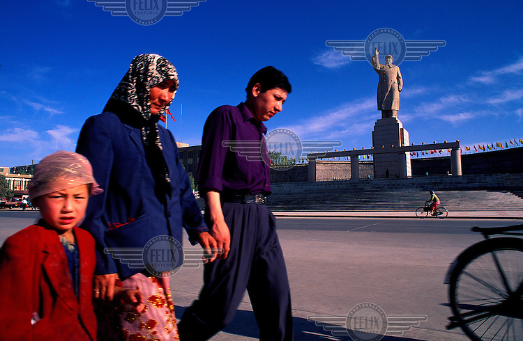 ©Chris Stowers/Panos Pictures..Muxlim family walking past the gleaming concrete statue of Chairman Mao in the Xinjiang, North-West China city of Kashgar.