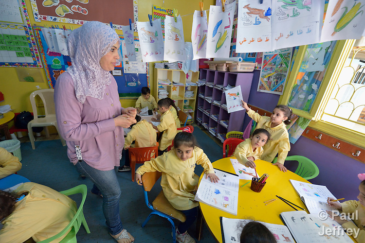 Hiyam Moussa helps children study in a school in the Sabra refugee camp in Beirut, Lebanon, run by the Department of Service for Palestinian Refugees of the Middle East Council of Churches. Most of the school's 148 students are Syrian refugees, but roughly one-third are Palestinian refugees and a few are poor children from the neighborhood. Lebanon hosts some 1.5 million refugees from Syria, and yet the government prohibits the establishment of large refugee camps, thus pushing many refugee families to search for housing in existing Palestinian refugee camps. This school is supported by the ACT Alliance.