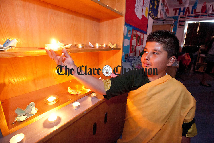 Dominik Makuna placing candles in the Thailand Room at Educate Together National School. Photograph by Declan Monaghan