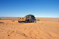 Four wheel drive parked on red sand dune, outback Australia