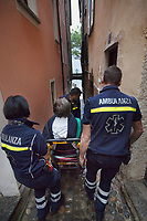Switzerland. Canton Ticino. Morcote. A senior man is carried down a narrow alley with an emergency medical chair. He will go by ambulance to hospital for medical examination. The elderly man is suffering from deep vein thrombosis (DVT), which is a blood clot in the deep veins of the leg. Team paramedics wears a blue uniforms and works for the Croce Verde Lugano. Both men (R)(C) are professional certified nurses, the woman (L) is a volunteer specifically trained in emergency rescue. The Croce Verde Lugano is a private organization which ensure health safety by addressing different emergencies services and rescue services. Volunteering is generally considered an altruistic activity where an individual provides services for no financial or social gain to benefit another person, group or organization. Volunteering is also renowned for skill development and is often intended to promote goodness or to improve human quality of life. 27.01.2018 © 2018 Didier Ruef