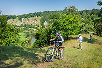 Deutschland, Bayern, Mittelfranken, Naturpark Altmuehltal, bei Solnhofen: Mountainbiker am Juratrockenhang mit der Felsgruppe Zwoelf Apostel, weiter unten fliesst die Altmuehl entlang | Germany, Bavaria, Middle Franconia, Nature Park Altmuehl Valley, near Solnhofen: mountain biker at rock formation 12 Apostles upon river Altmuehl