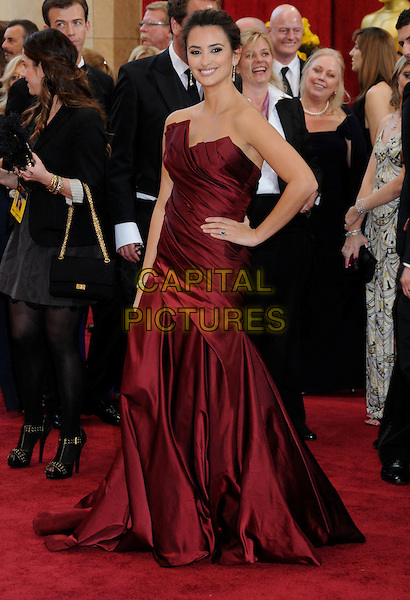 PENELOPE CRUZ .wearing Donna Karen .Attending the 82nd Annual Academy Awards held at the Kodak Theatre, Hollywood, California, USA, .March 7th, 2010..oscars arrivals full length red maroon strapless long maxi gown dress hand on hip engagement ring smiling burgundy side  .CAP/ADM/BP.©Byron Purvis/Admedia/Capital Pictures