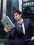 Portrait of a young businessman in a suit using Apple iPad tablet computer in city downtown with office buildings in the background. Toronto, Ontario, Canada.