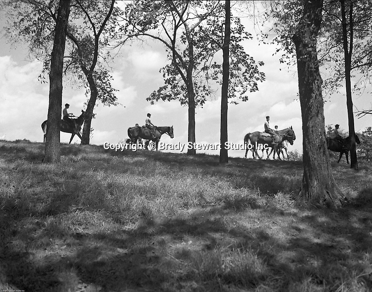 Pittsburgh PA: View of boys  riding Horses in Schenley Park - 1952.  Created in 1889 with land donated by heiress Mary Schenley, the park now contains 456 acres of trails, woods, and attractions.   The main attractions are Phipps Conservatory, Flagstaff Hill, Golf Course, Horse Stables and swimming pool.