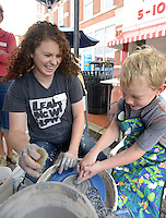 NWA Democrat-Gazette/BEN GOFF @NWABENGOFF<br /> Faith Whittle, studio technician with Community Creative Center, helps Jack Morris, 8, of Bentonville learn to spin pottery on Sunday Aug. 23, 2015 during Sidewalk Sundays with Community Creative Center at the Walmart Museum in Bentonville. Community Creative Center, located in the Walton Arts Center's Nadine Baum Studios in Fayetteville, offers visual arts classes, workshops and camps for children and adults.