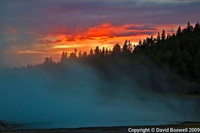 The setting sun lights the clouds in Yellowstone National Park with Black Warrior Lake in the foreground.