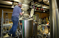 NWA Democrat-Gazette/DAVID GOTTSCHALK Chris Courtney, shift Brewer at Fossil Cove Brewery in Fayetteville, stirs the mash Tuesday, April 10, 2018, in a mash tun at the Birch Avenue location in Fayetteville. The brewery will expand moving some of it's operation about half a block away to a facility on Poplar Street.