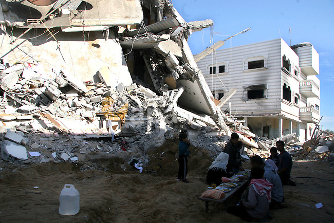 Palestinians eat on the rubble of their building in Beit Lahia on the Gaza Strip. January 21, 2009.  Photographer:  APAIMAGES PHOTO / Ashraf Amra