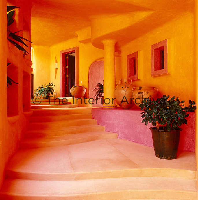 The use of striking pink and orange colours emphasises the sculptural design of this entrance hallway