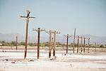 Salt-encrusted utility poles at a former lake-shore resort (spa) at the southern end of the Salton Sea, Salton Sea, Calif.