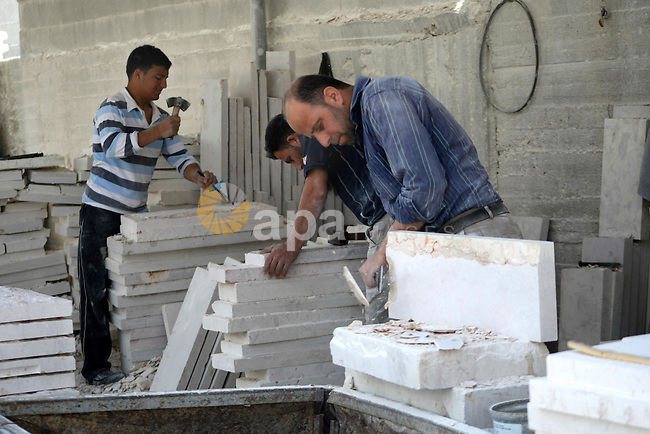 Palestinian labourers work at a marble workshop on the eve of Labor Day, in the West Bank city of Hebron April 30, 20130. Stone and marble factories and quarries, located mainly in the West Bank cities of Bethlehem and Hebron, are at the core of the Palestinian industrial sector. According to the Union of Stone and Marble Industry, the industry employs about 16,000 administrative, skilled and unskilled labourers. Photo by Mamoun Wazwaz