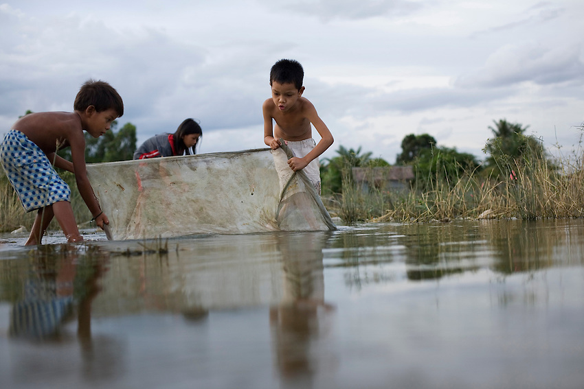 Children that face eviction from the Boeung Kak Lake area in central Phnom Penh try to catch fish in a net, Phnom Penh, Cambodia, July 30, 2010.