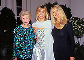 Australian singer, songwriter and actress Olivia Newton-John, center, arrives for the State Dinner hosted by United States President George H.W. Bush and first lady Barbara Bush honoring President Václav Havel of Czechoslovakia at the White House in Washington, DC with her mother, Irene Newton-John, left, and sister, Rona Newton-John, right, on October 22, 1991.<br /> Credit: Ron Sachs / CNP